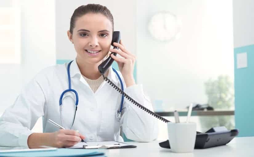 Young female doctor sitting at her desk and talking on the phone
